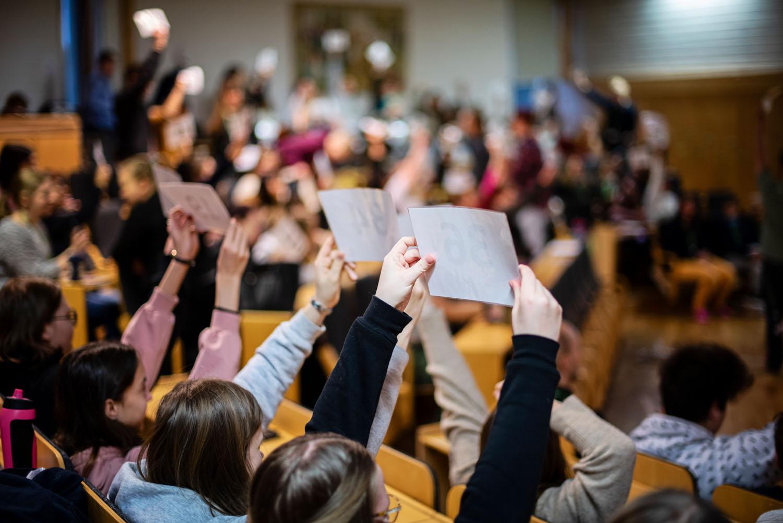 Ungdomar sitter i en sal och håller upp plakat som de rösta med
